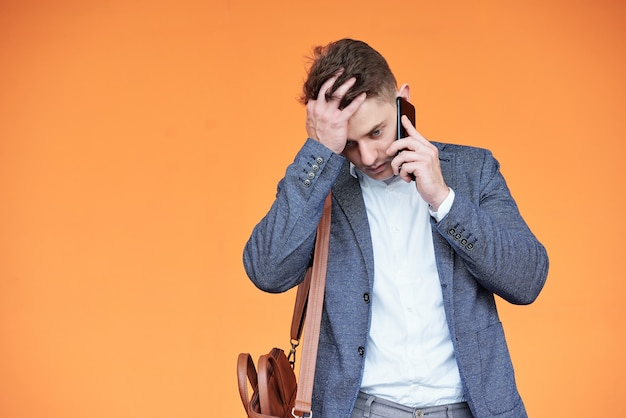 Shocked stressed young businessman receiving bad news on the phone