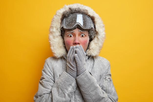 충격을받은 스트레스를받은 젊은 여성은 손으로 입을 덮고 후드 재킷을 입고 흰 서리로 덮인 장갑은 스칸디나비아의 계절 야외 활동 중에 추위를 느낍니다.