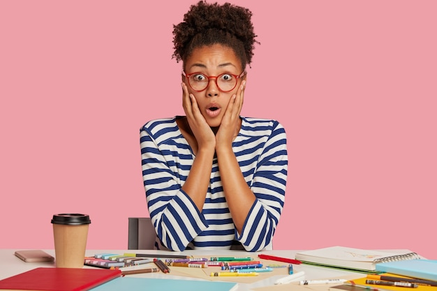 ピンクの壁に向かって机でポーズをとってショックを受けた学生の女の子
