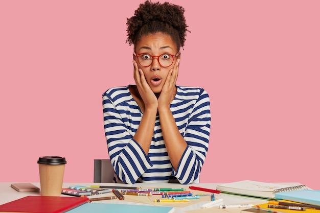 Ragazza studentessa scioccata in posa alla scrivania contro il muro rosa