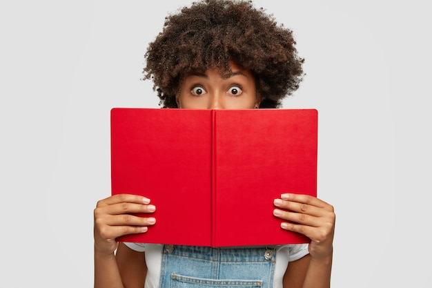 Shocked student with afro haircut, holds opened red book in front, covers half of face
