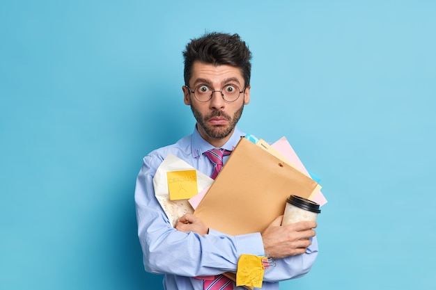 Shocked student with thick bristle prepares for studying courses holds papers and disposable cup of coffee dressed formally. stunned employee prepares accounting project for boss works in office