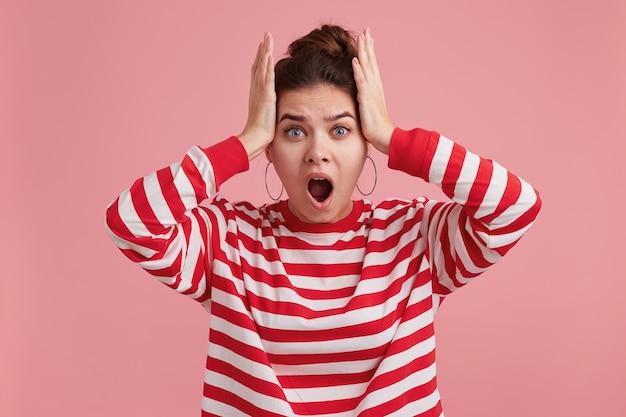 Шокированная ошеломленная молодая женщина держит рот широко открытым, смотрит в ужасе и носит полосатый лонгслив.