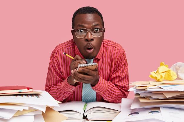Scioccato stupefatto maschio in abiti formali, ascolta attentamente le informazioni, scrive note nel diario a spirale con la matita, cerca di ricordare di tutto