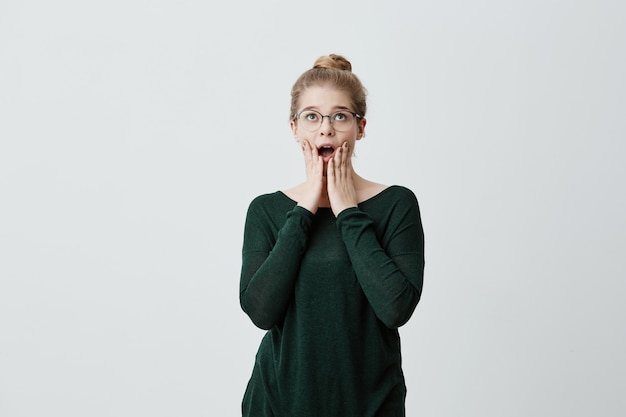 Shocked stupefied young blonde female wearing eyeglasses looks with widely opened mouth, keeps hands on cheeks, doesn`t believe in her failure, has puzzled and frustrated look