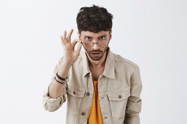 Шокированный стильный бородатый парень позирует у белой стены