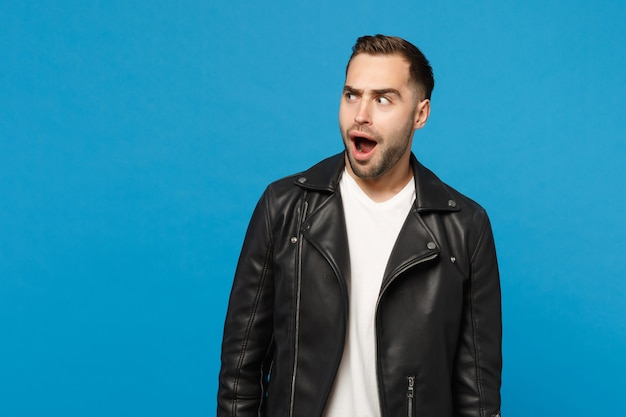 Shocked stylish young bearded man in black leather jacket white t-shirt looking aside isolated on blue wall background studio portrait. people sincere emotions lifestyle concept. mock up copy space.