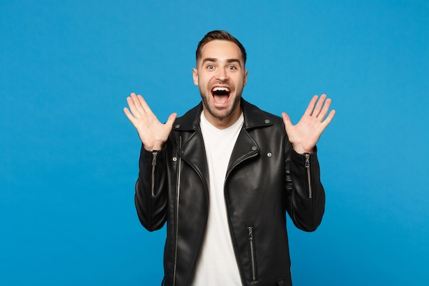 Shocked stylish young bearded man in black leather jacket white t-shirt looking camera isolated on blue wall background studio portrait. people sincere emotions lifestyle concept. mock up copy space.