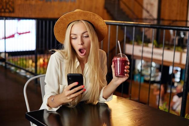 スマートフォンを手にテーブルに座って、大きな口を開けて画面を驚かせて見ている、ショックを受けたスタイリッシュな若い長い髪のブロンドの女性は、シティカフェのインテリアの上でポーズをとる