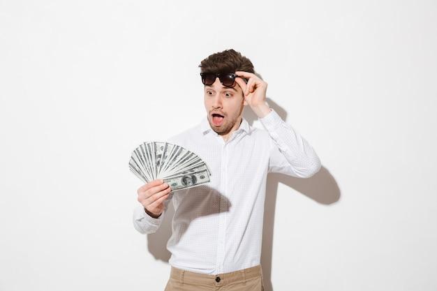 黒いサングラスを脱いで、影で白い壁に分離された興奮でお金のドル札のファンを見てシャツでショックを受けた成功した男