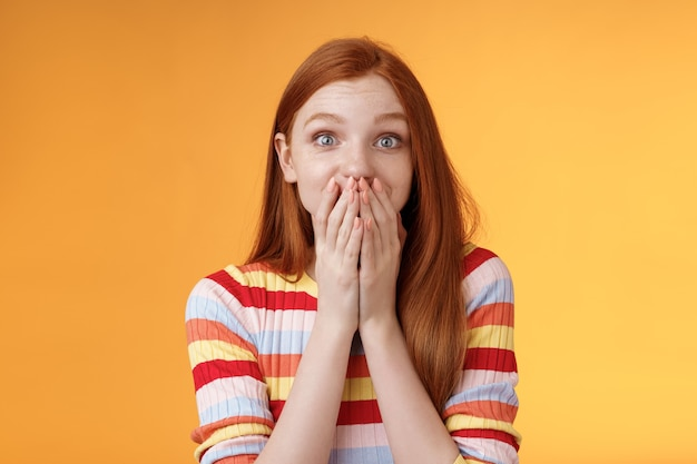 Shocked surprised attractive cute redhead girl receive awesome chance smiling impressed gasping cover mouth palms wide eyes excited happily reacting incredible good news, standing orange background.