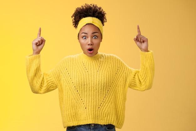Шокированная удивленная эмоциональная афро-американская студентка с отвисшей челюстью и широко раскрытыми глазами узнает удивительные новости, указывая поднятыми вверх пальцами, задыхаясь, пораженная, безмолвная стоя на желтом фоне.