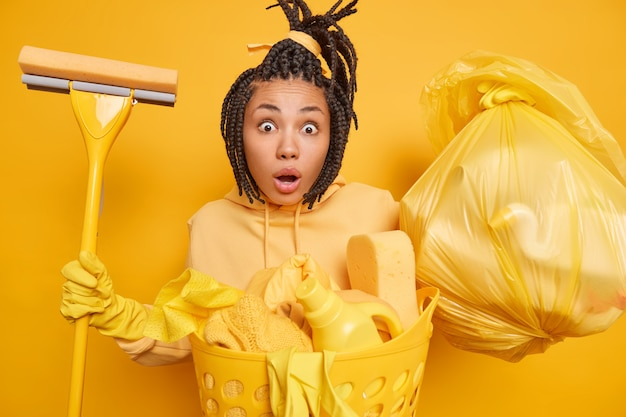 Shocked surprised ethnic housemaid wears rubber gloves for hand protection holds mop trash bag