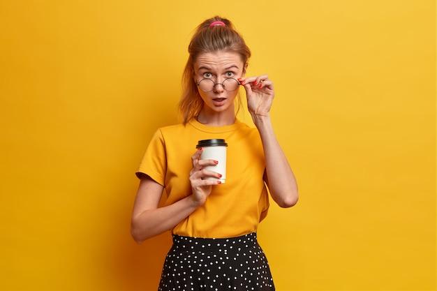 놀란 유럽 여학생은 안경을 들여다보고, 테이크 아웃 커피와 함께 포즈를 취하고, 놀라운 소식을 듣고, 눈을 믿을 수없고, 캐주얼 한 옷을 입습니다.