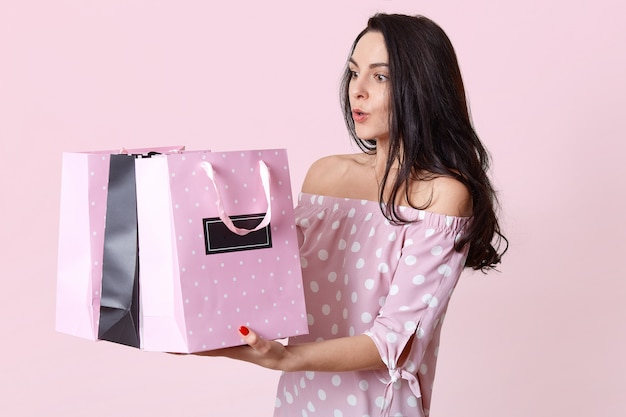 Shocked surprised european young woman holds bags, astonished to recieve many presents, dressed in polka dot dress, wants to open gift, poses on pink. people and shopping concept