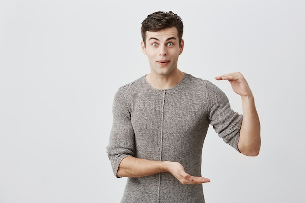 Shocked surprised excited european handsome male model wearing sweater with dark hair and bugged eyes showing size of something with hands, gesturing. body language concept