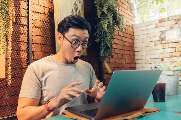 Shocked and surprised face of man works on his laptop in the cafe.