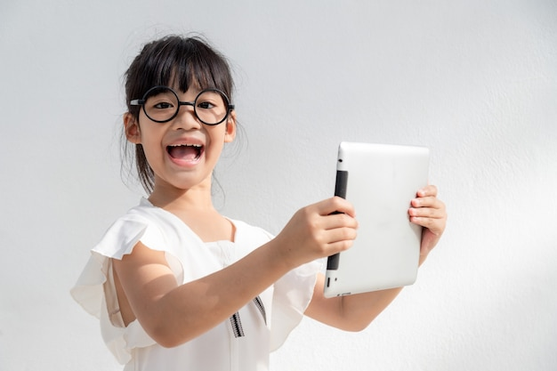 Shocked and surprised little girl on the internet with digital tablet computer concept for amazement