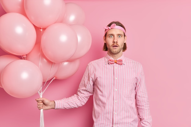 L'uomo sorpreso scioccato tiene un mazzo di palloncini sente notizie incredibili indossa una camicia elegante con fascia per capelli con papillon celebra qualcosa da fare alla festa di compleanno isolata sopra il muro rosa