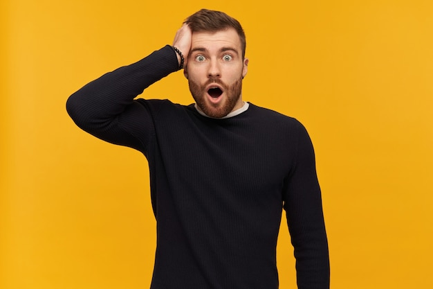 Shocked surprised young man with beard and opened mouth in black longsleeve keeps hand on head and looking at front over yellow wall