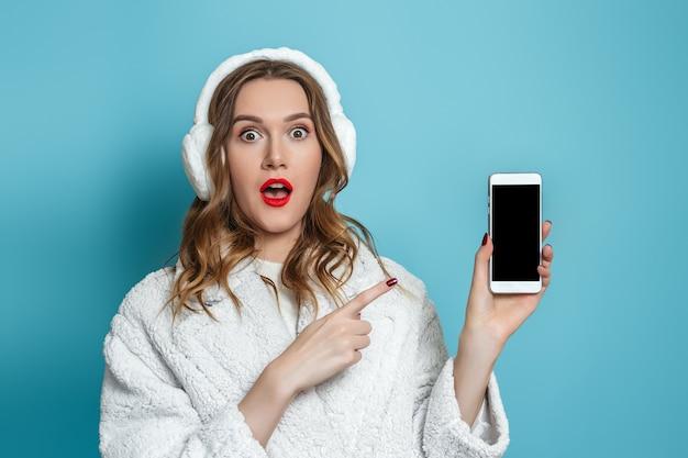 흰색 인조 모피 코트 포인트 손가락 블루 스튜디오 배경에 고립 된 휴대 전화 화면에서 충격 된 놀된 젊은 여자.