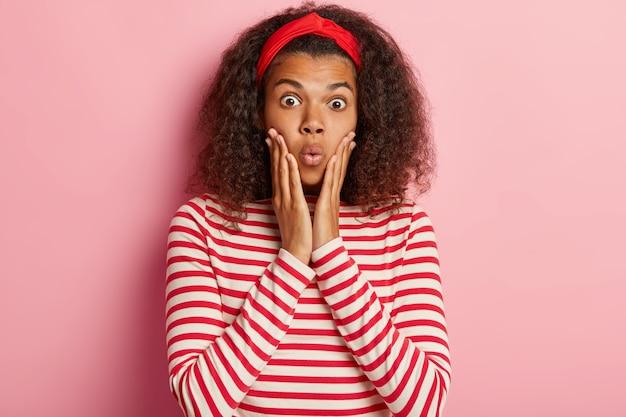 縞模様の赤いセーターでポーズをとって巻き毛のショックを受けた10代の少女
