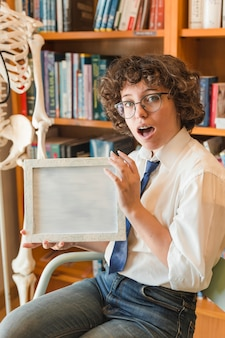 Shocked teenager showing frame in library