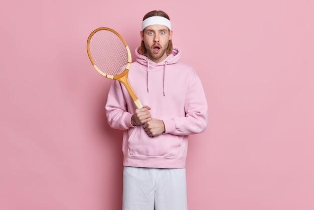 Il tennista scioccato tiene la racchetta indossa una felpa con fascia per la testa stordito per perdere la concorrenza conduce uno stile di vita attivo.