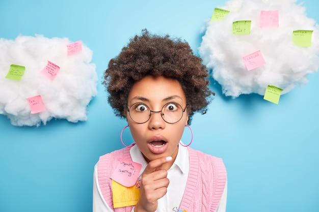 ショックを受けた恐怖の女子学生は重要なメモを使用します紙のステッカーを使用しますポストは深く驚いているあごに手を保ちます青い壁の上に隔離された丸い眼鏡のフォーマルな服を着ています