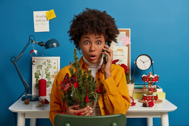 Shocked terrified woman with afro hairstyle, holds beautiful decorated christmas tree, forgets to buy something necessary for holiday