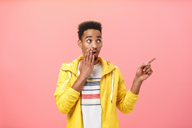 Shocked thrilled african american male with beard and afro haircut saying wow with opened mouth and palm on lip pointing and gazing at upper right corner intrigued over pink background