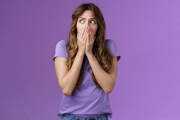 Шокированная робкая неуверенная обеспокоенная кудрявая женщина смотрит в сторону ошеломленная испуганная задыхающаяся прикрытие рот держать ладони прижатые лицо взгляд влево испуганный обеспокоенный паника фиолетовый фон