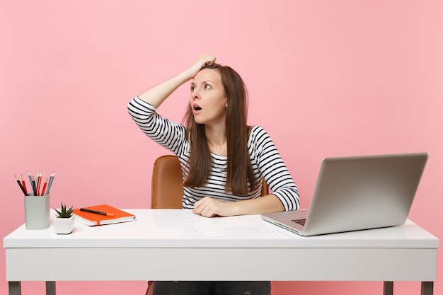 Shocked tired woman in perplexity clinging to head looking up sit, work at white desk with contemporary pc laptop isolated on pastel pink background. achievement business career concept. copy space.