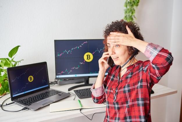 충격을 받은 상인 여성은 휴대 전화로 통화하는 동안 암호 화폐 시장의 충돌로 인해 머리에 손을 얹었습니다.