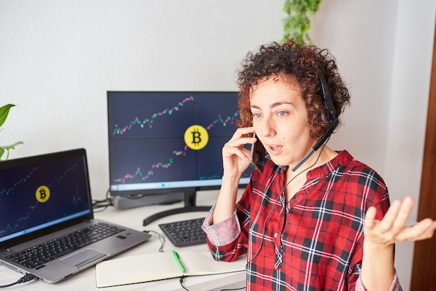 Shocked trader woman talks on the mobile phone with some screens with cryptocurrency data on her computer screens