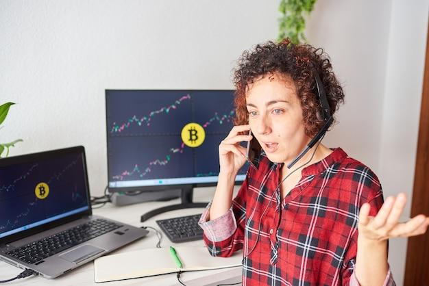 충격을 받은 상인 여성은 컴퓨터 화면에 암호 화폐 데이터가 있는 일부 화면으로 휴대 전화로 이야기합니다.