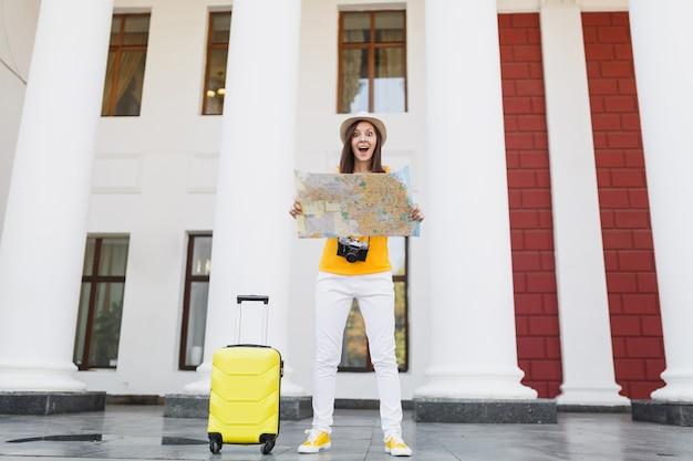 スーツケースのレトロなビンテージ写真カメラでカジュアルな服を着てショックを受けた旅行者の観光客の女性は、屋外の都市の都市地図を保持します。週末の休暇で旅行するために海外旅行する女の子。観光の旅のライフスタイル。