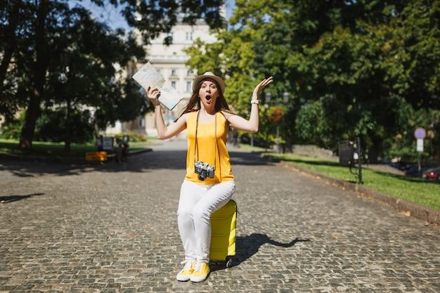노란색 옷을 입은 충격적인 여행자 관광 여성, 여행 가방에 앉아 있는 모자는 도시 야외에서 손을 펼치고 있는 도시 지도를 들고 있습니다. 주말 휴가를 여행하기 위해 해외로 여행하는 소녀. 관광 여행 라이프 스타일.
