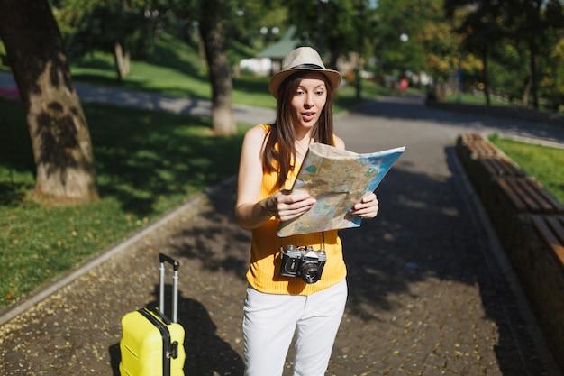 노란색 여름 캐주얼 옷을 입은 충격적인 여행자 관광 여성, 도시 야외에서 도시 지도를 보고 있는 여행 가방이 달린 모자. 주말 휴가를 여행하기 위해 해외로 여행하는 소녀. 관광 여행 라이프 스타일.