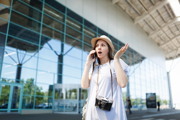 Shocked traveler tourist woman with retro vintage photo camera spread hands talk on mobile phone call friend