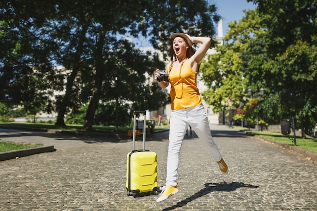 Shocked traveler tourist woman with suitcase screaming clinging to head holding retro vintage photo camera jumping in city outdoor. girl traveling abroad on weekend getaway. tourism journey lifestyle.