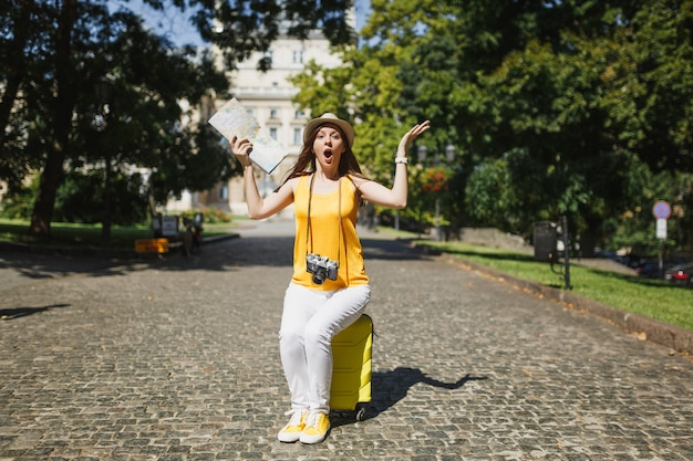 Shocked traveler tourist woman in yellow clothes, hat sitting on suitcase hold city map spreading hands in city outdoor. girl traveling abroad to travel on weekend getaway. tourism journey lifestyle.