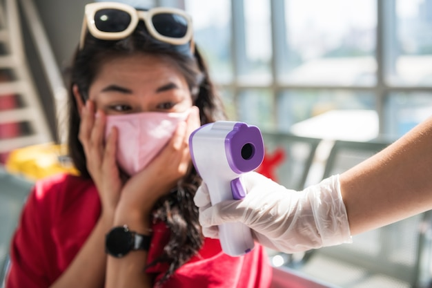 Shocked traveller with mask see her high body temperature from medical infrared thermometer on officer hand. woman in airport terminal fail of flight due to potential of corona or covid-19 virus.