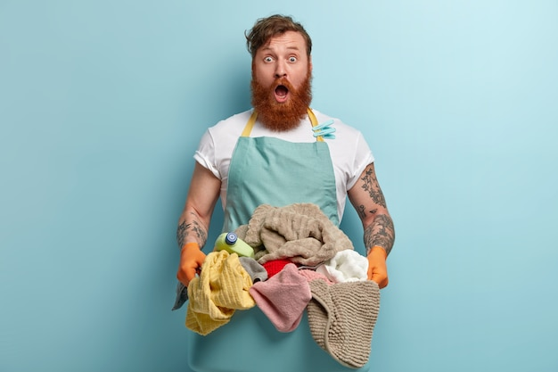 カジュアルな青いエプロンでショックを受けた問題を抱えた赤い髪のひげを生やした男は、展開された洗濯物の洗面器を保持します