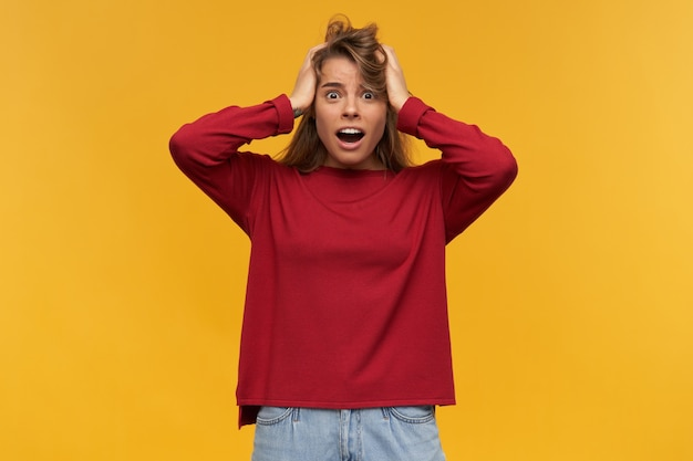 충격을받은 불만족 금발 소녀는 분개하게 보이며 입을 크게 벌리고 분노로 얼어 붙고 캐주얼 한 빨간 스웨터를 입고