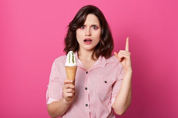 Шокированная неудовлетворенная модель широко раскрывает рот и глаза от удивления, поднимает указательный палец, с негодованием смотрит прямо в камеру, держит мороженое в одной руке, носит полосатую рубашку.