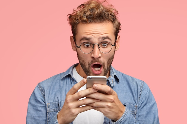 Shocked unshaven man looks surprisingly and with terrified expression at screen of smart phone, uses free wifi for messaging in social networks, reads awful news via internet. omg concept