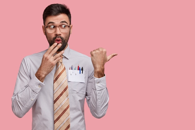 Shocked unshaven young man covers mouth, looks in amazement, dressed in formal clothes with tie, points with thumb at copy space