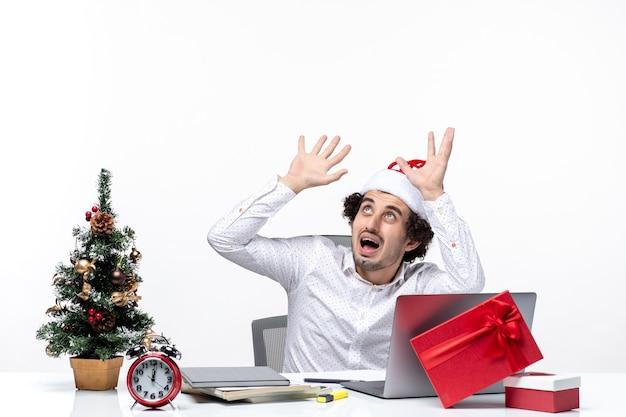 Scioccato giovane uomo d'affari insicuro con buffo cappello di babbo natale guardando sopra in ufficio su sfondo bianco