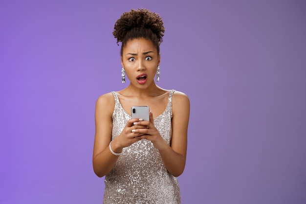 Shocked upset african-american woman in glittering stylish expensive dress drop jaw cringing disappointed receive terrible upsetting message holding smartphone look concerned blue background.